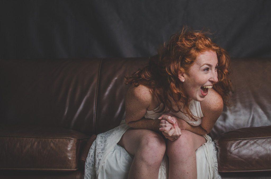 Imagem de uma moça de cabelos longos e ruivos. Ela usa um vestido branco de renda e está sentada em um sofá de couro marrom. Ela está feliz e ri muito.