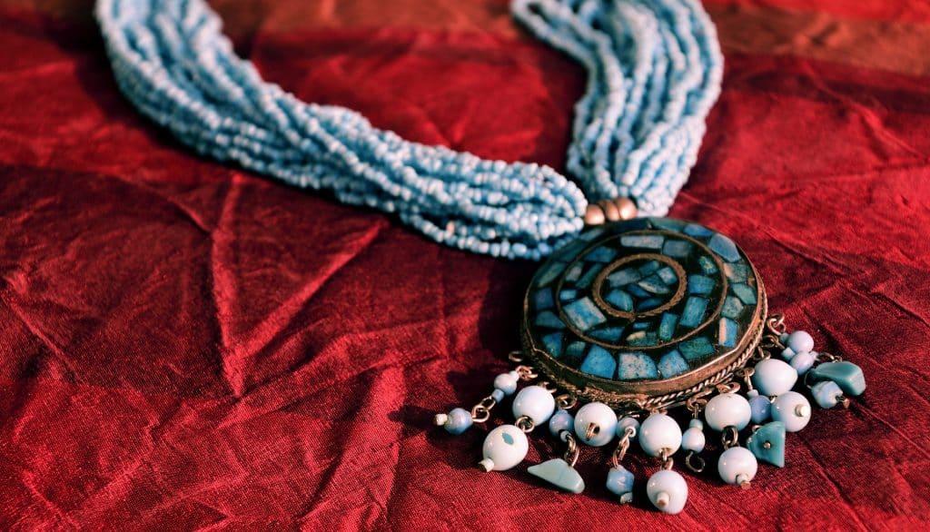 Imagem de um amuleto em formato de colar. Ele é feito com vários tipos de pedras nas cores azul escuro e azul claro.
