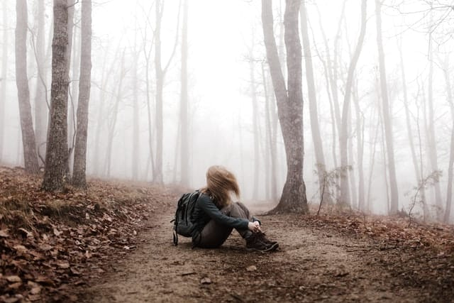 Mulher branca sentada no meio da floresta nebulosa.