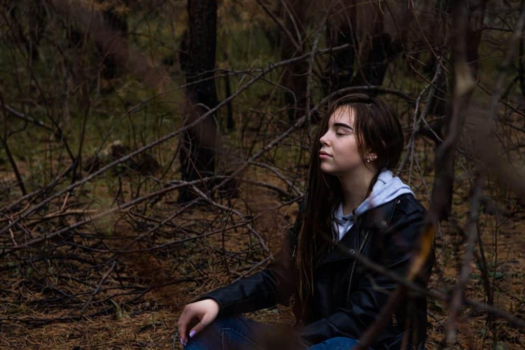 Mulher branca sentada na floresta com os olhos fechados.