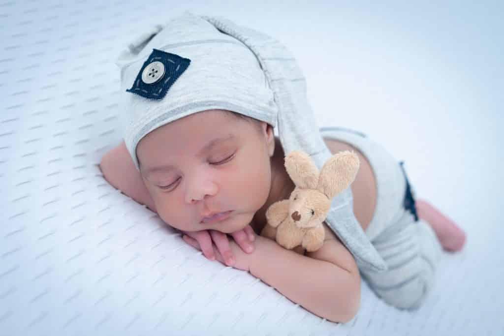 Imagem de um lindo bebê recém nascido dormindo. Ele está deitado de bruços sobre uma cama com lençol branco. Ele usa uma touca cinza moderna e ao lado dele um coelhinho de pelúcia complementa a imagem.