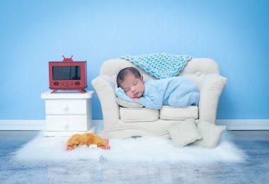 Imagem de um quarto infantil decorado com uma poltrona brnaca, um tapete de pelo, um criado de duas gavetas com uma TV de pequena polegada sobre ele. No sofá temos um recém nascido dormindo bem gostoso.