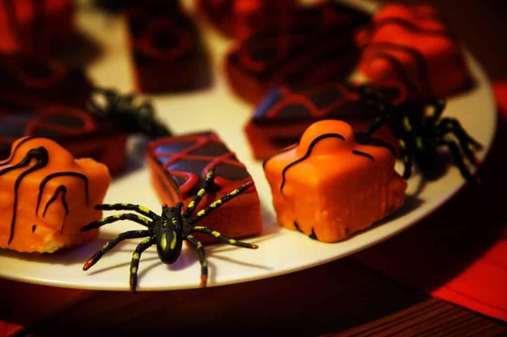 Imagem de um prato branco de porcelana repleto de doces decorados com aranhas e outros tipos de insetos para serem servidos no dia do Halloween.