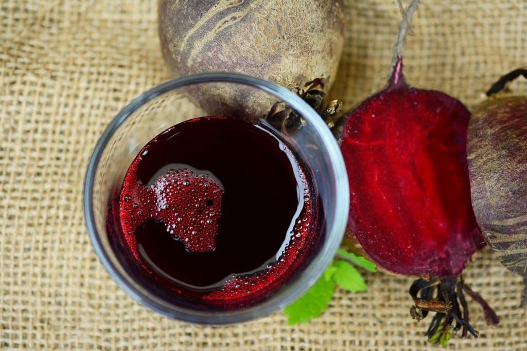 Imagem de um copo com suco detox roxo feito com beterraba.