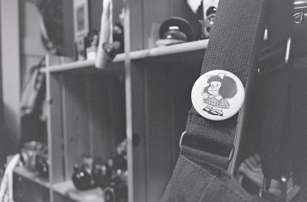 Alça de bolsa com bottom estampado pela personagem Mafalda.