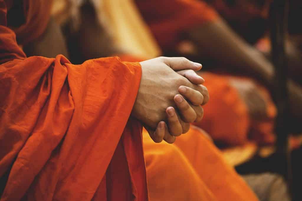 Imagem de um monge sentado e meditando. Ele veste um longo vestido alaranjado e está com as suas mãos entrelaçadas.