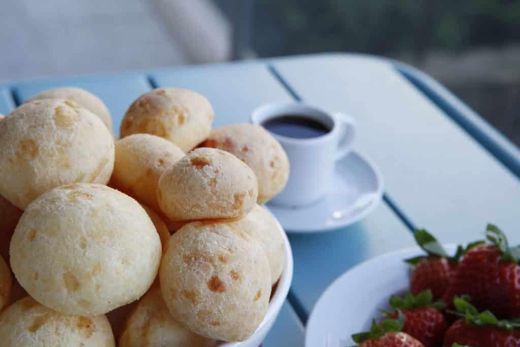 Imagem de um prato com pão de queijo feito com batata-doce. Os pães já estão assados. Ao lado do prato uma xícara de café.