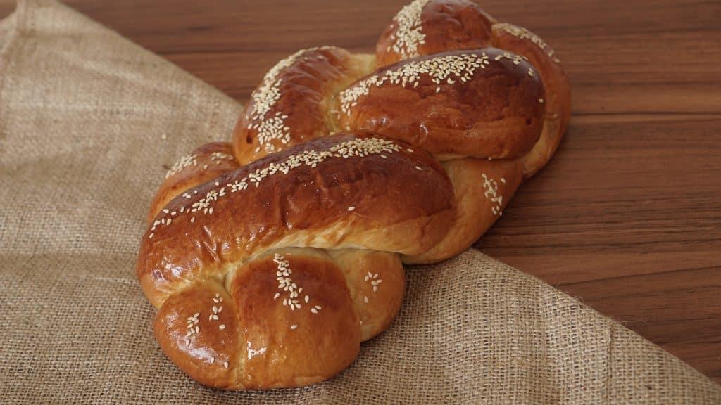 Imagem de um pão chalá todo trançado e decorado com gergelim, disposto sobre uma mesa de madeira.