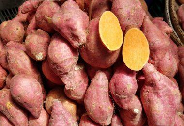 Imagem de uma bancada com muitas batata-doce e sobre elas uma cortada ao meio.