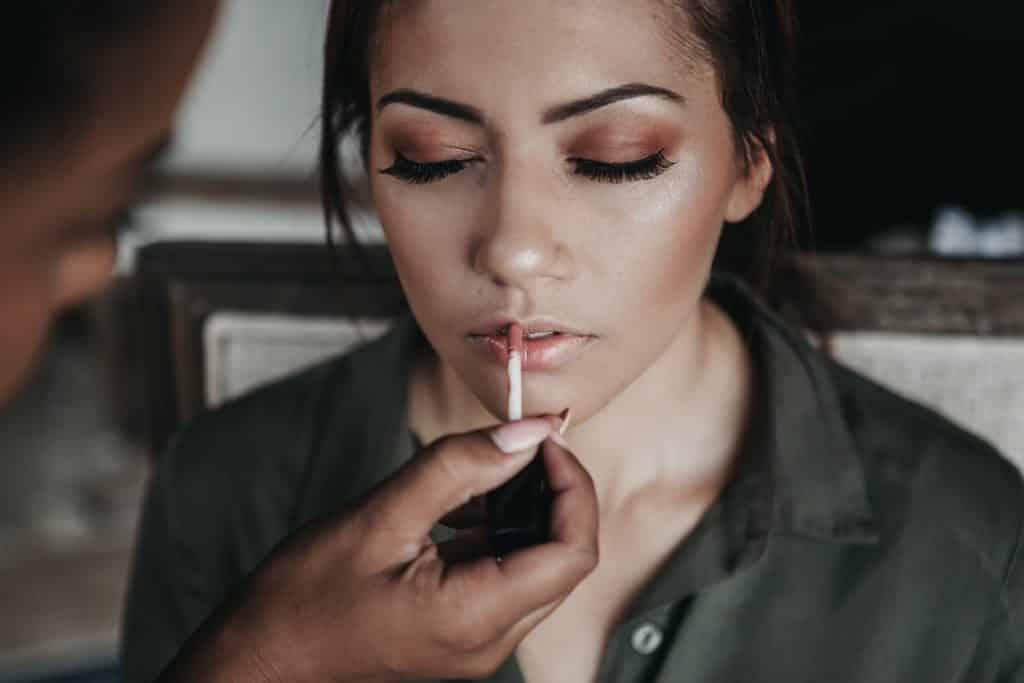 Mulher negra passando brilho labial em mulher branca.