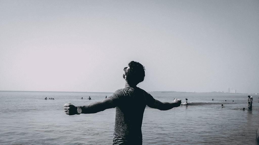 Homem com os braços erguidos na praia
