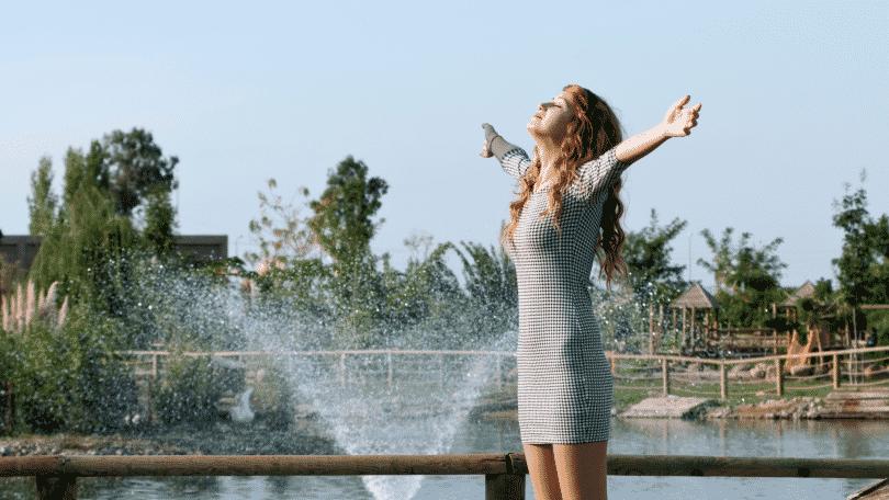 Mulher ruiva em um parque com os braços erguidos e sorrindo
