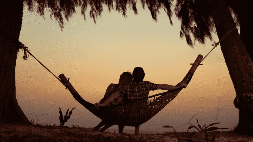 Silhueta de casal sentados em uma rede observando o pôr do sol