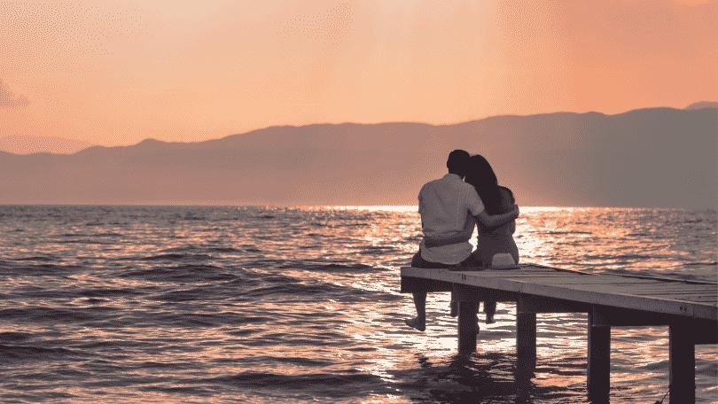 Casal sentado em um deck observando o pôr do sol