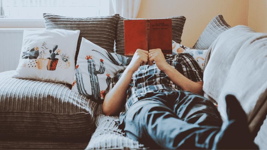 Homem deitado no sofá lendo um livro