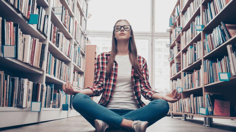 Garota de óculos meditando na biblioteca