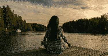 Silhueta de uma mulher meditando em um deck na frente do rio