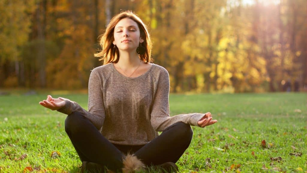 Mulher meditando na grama