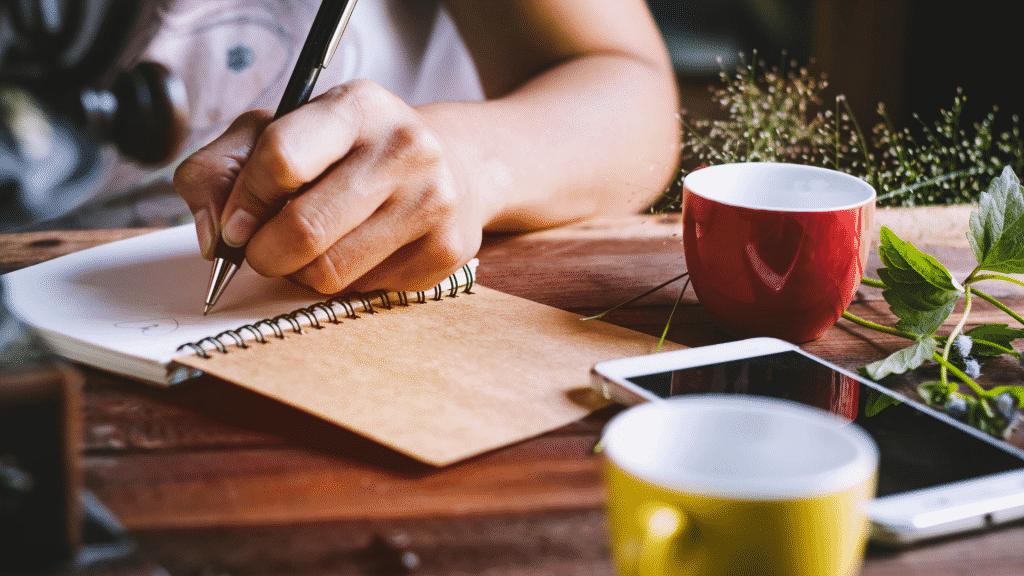 Mulher trabalhando e escrevendo em caderno com canecas sobre a mesa
