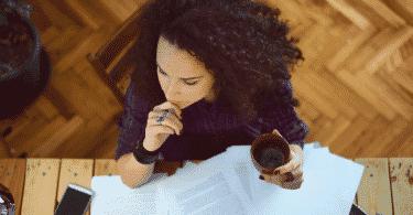 Mulher trabalhando enquanto toma café em frente a mesa com papelada