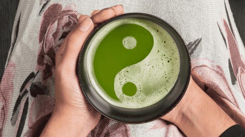 Par de mãos segurando chá com símbolo do ying yang