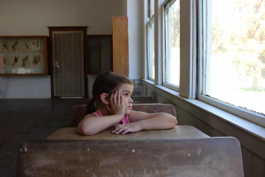Imagem de uma criança sentada em uma carteira dentro de uma sala de aula, próxima a uma janela. Ela está meio triste e olhando para fora,
