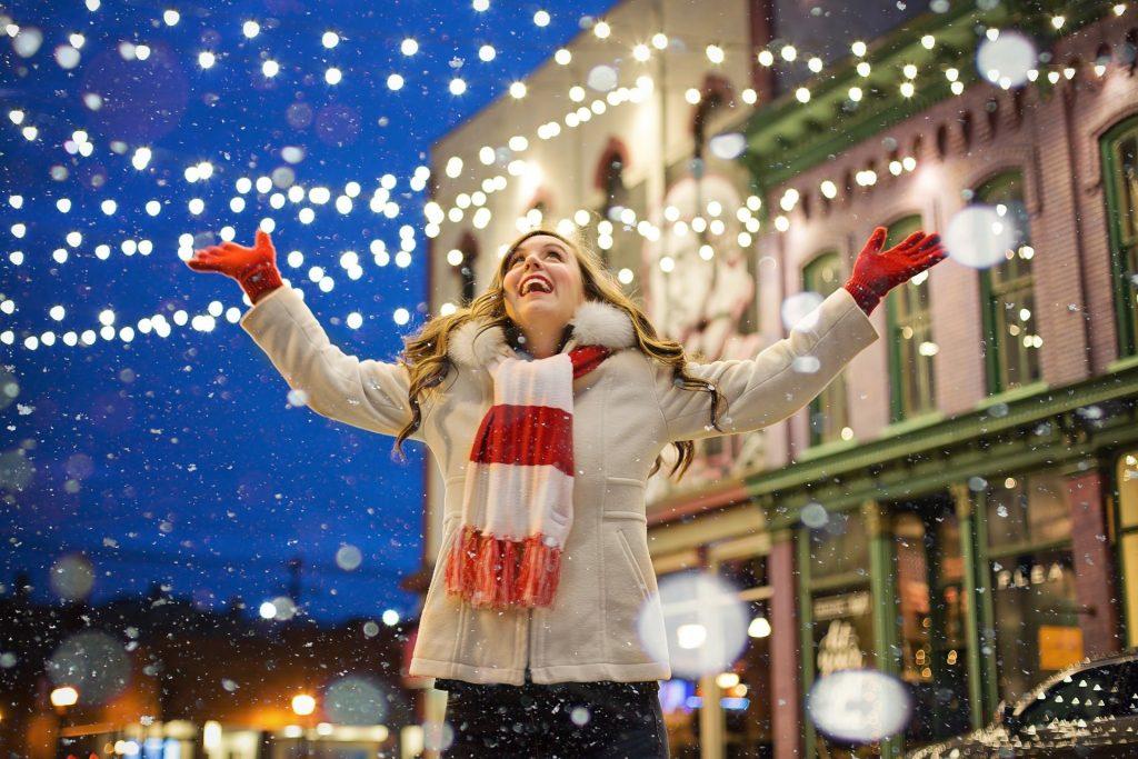 Imagem de uma linda e feliz mulher em uma rua iluminada para celebrar a chegada do natal. Ela usa um casaco de frio na cor bege, um cachecol nas cores branco e vermelho e também luvas vermelhas.