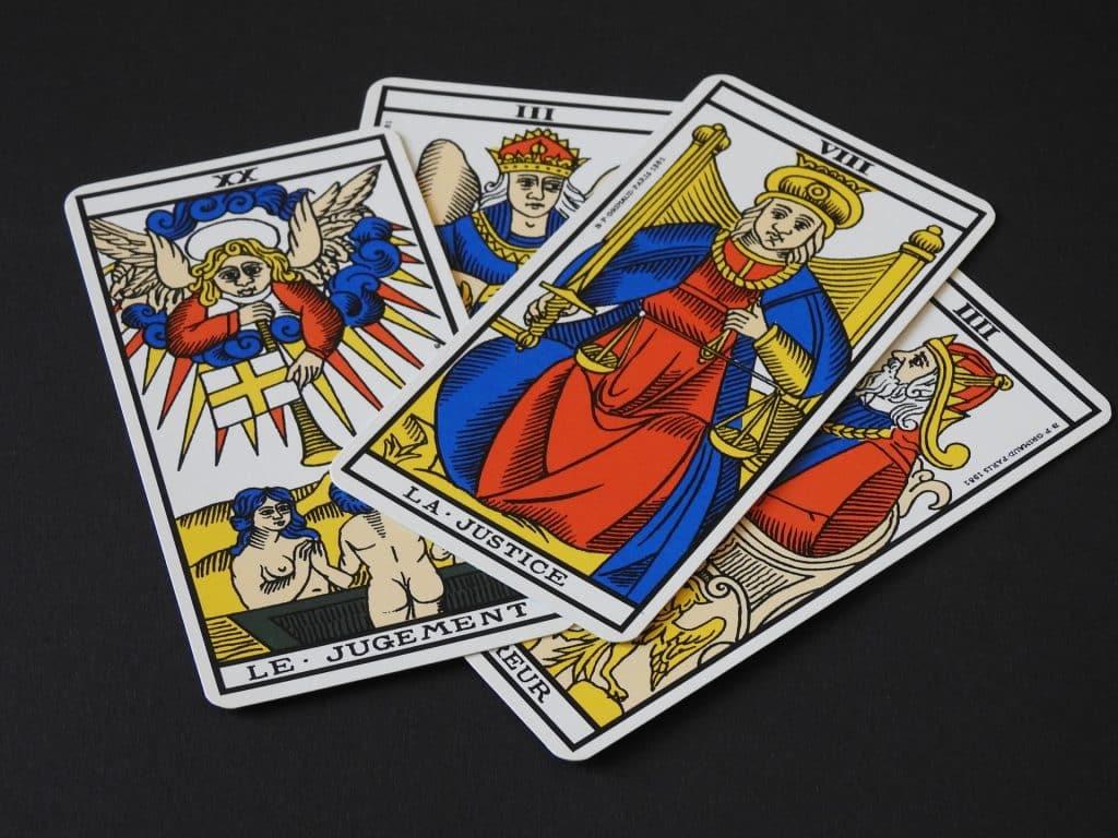 Imagem de fundo preto e em destaque quatro cartas de tarot entre elas a carta da justiça e do julgamento.
