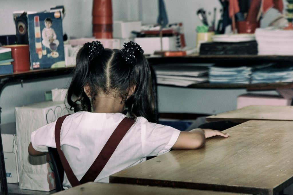Imagem de uma criança em uma sala de aula. Ela está sentada de costas. Usa o uniforme escolar com camisa branca e jardineira na cor vinho.