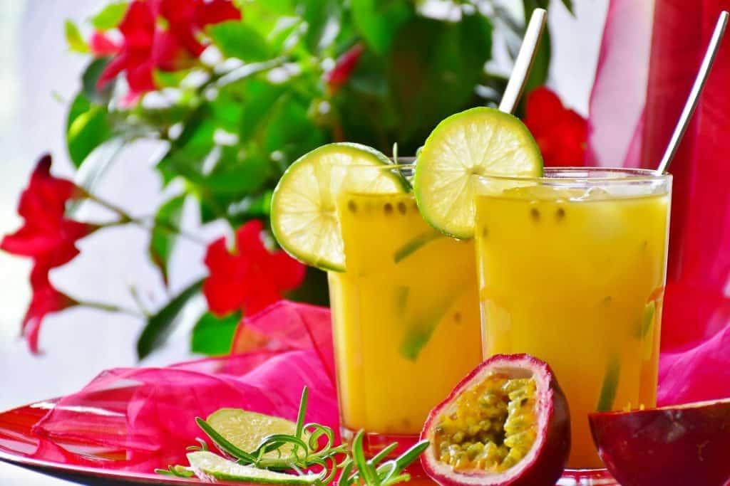 Imagem de dois copos de suco detox feitos com frutas amarelas. Os copos estão decorados com fatias de limão e estao sobre uma mesa decorada com um tecido de voal na cor rosa.