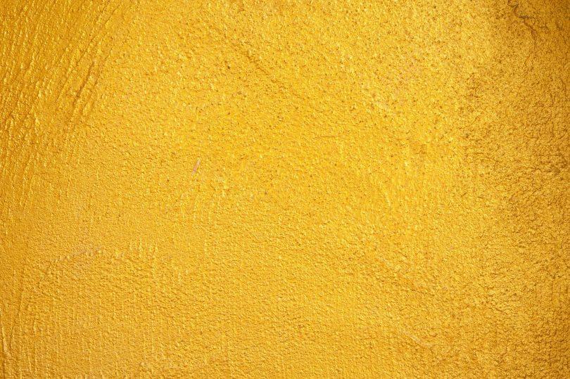 Imagem de uma parede texturizada e pintada na cor amarela.