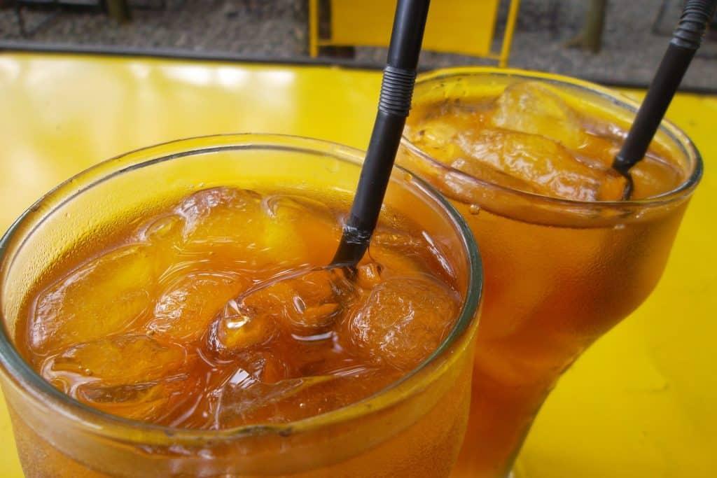 Imagem de dois copos de chá detox feito com gengibre e abacaxi servidos bem gelados.
