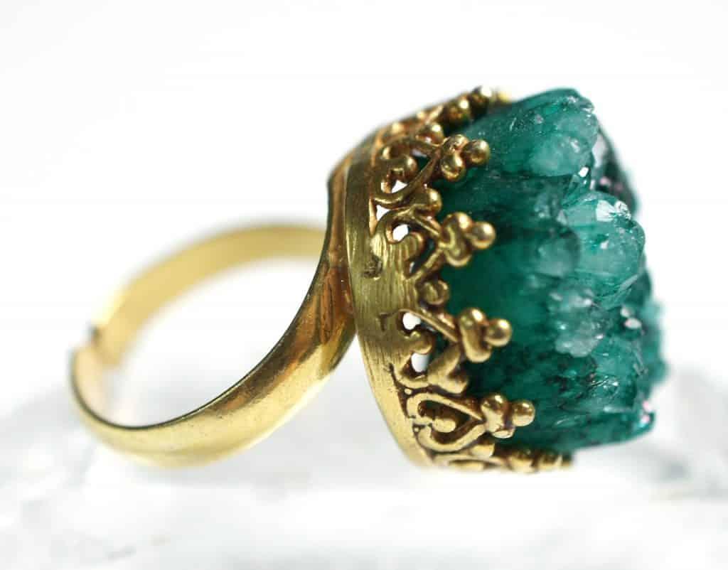 Imagem de um lindo anel de ouro com uma grande pedra de quartzo verde.