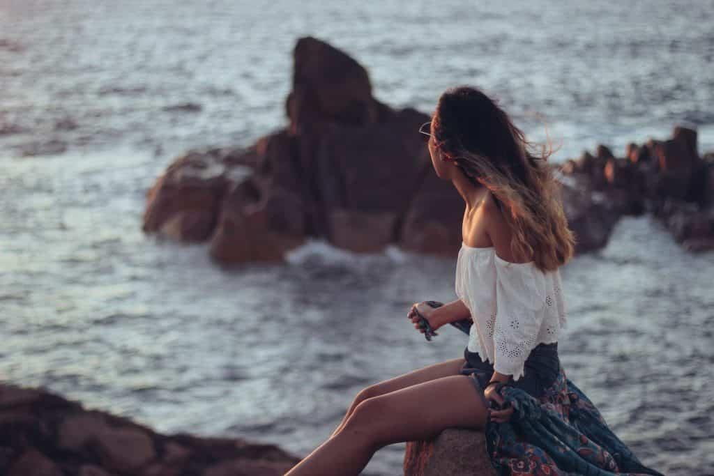 Mulher branca sentada numa rocha na praia.