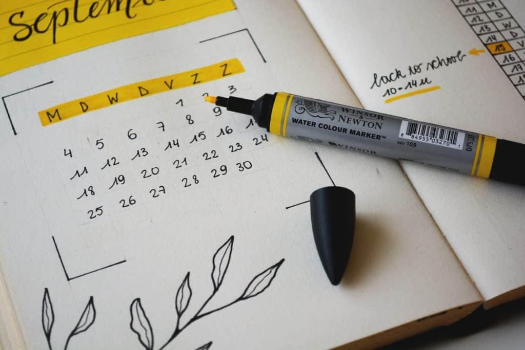 Caderno com desenhos e marca texto amarelo.