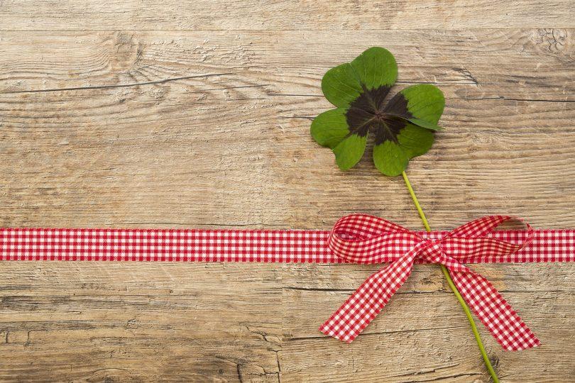 Imagem de um lindo trevo de quatro folhas amarrado a uma fita vermelha em formato de um laço.