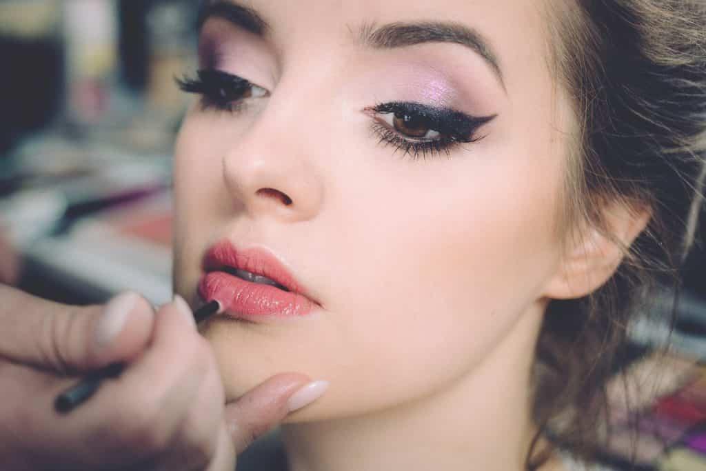 Mão feminina passando brilho labial nos lábios de mulher branca.