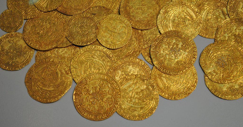 Imagem de muitas moedas de ouro dispostas sobre uma mesa de fundo cinza.