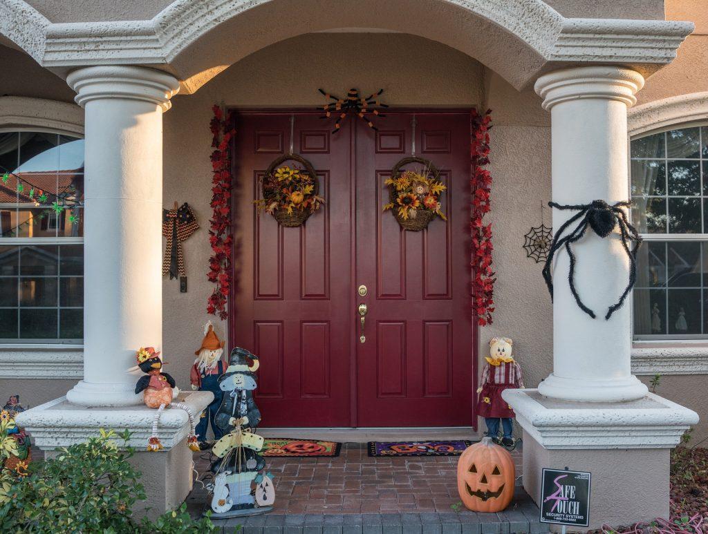 Imagem de uma fachada residencial com uma porta bem grande e toda decorada para a festa de Halloween.