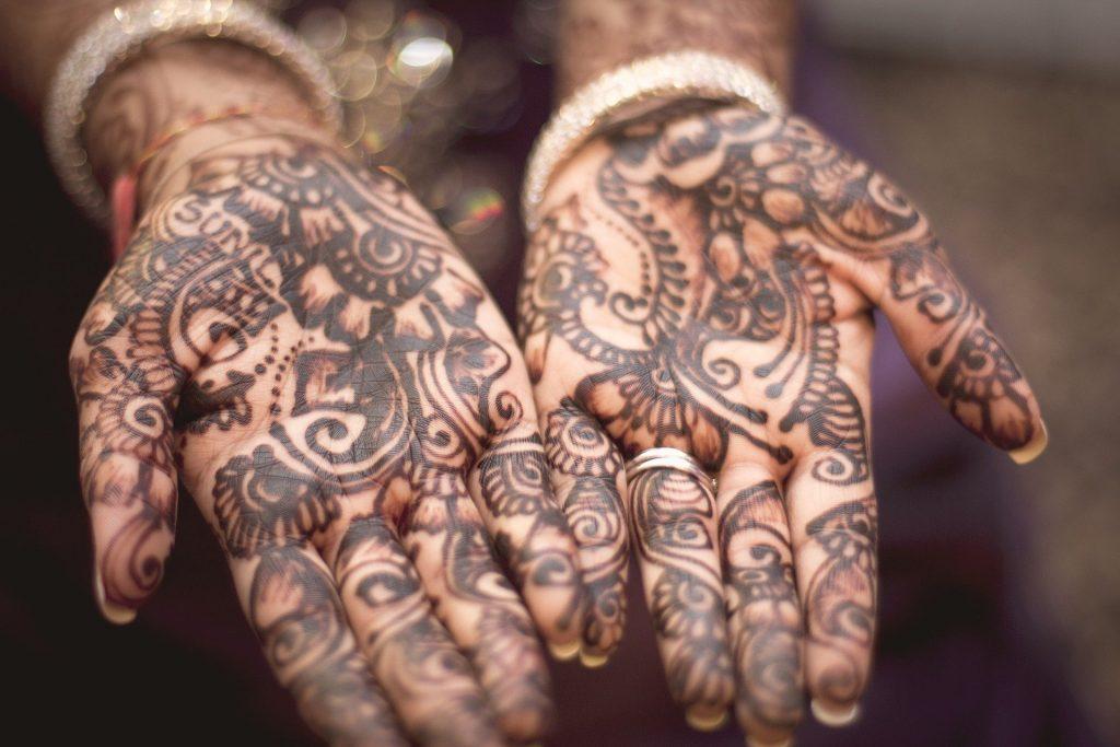 Imagem da palma das mãos de uma mulher e ambas estão tatuadas de forma total.