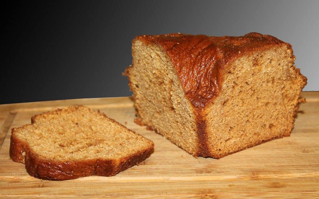 Imagem de um bolo de mel cortado ao meio e ao lado uma fatia, dispostos sobre uma tábua de madeira.