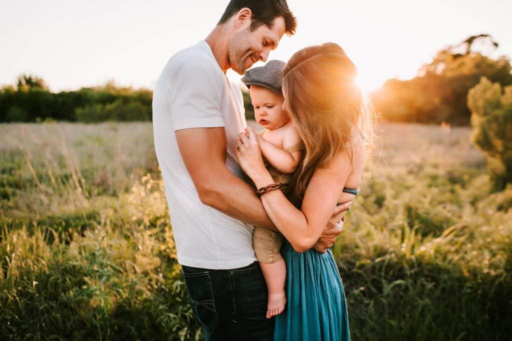 Homem e mulher brancos segurando bebê num campo.