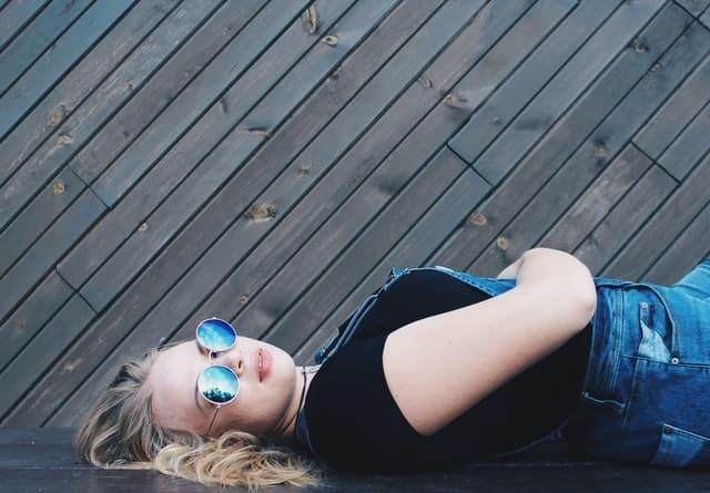 Mulher branca e loira deitada de barriga pra cima, usando óculos de sol azuis.