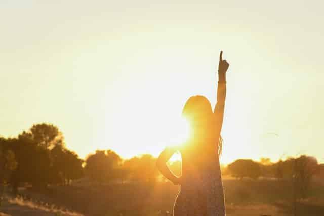 Silhueta de mulher com mão levantada e sol ao fundo refletindo