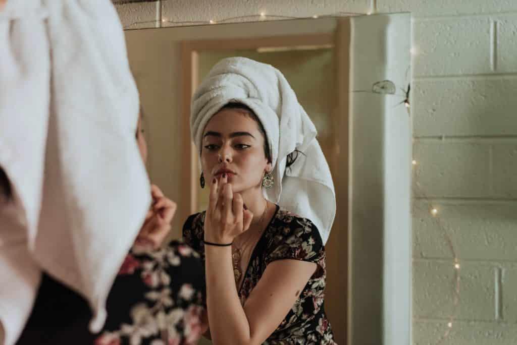 Mulher branca de toalha na cabeça e dedo anelar no lábio.