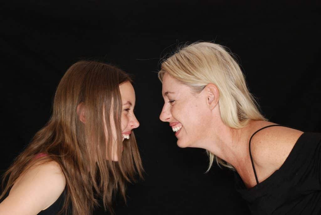 Imagem de mãe e filha, ambas vestem uma blusa preta. Elas estão de frente uma para outra e riem muito.