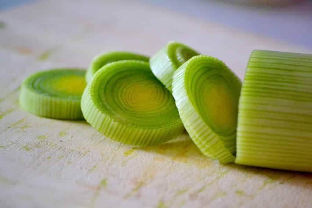 Imagem de um pedaço de alho poró cortado em rodelas, disposto em uma tábua de madeira.
