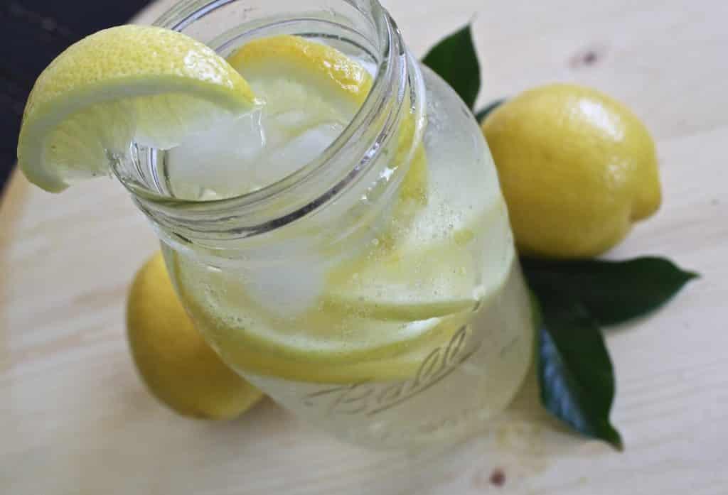 Imagem de uma jarra de vidro com chá de alecrim com capim-limão. A jarra está decorada com limão cortado ao meio e ao lado dela, limões decoram a mesa.