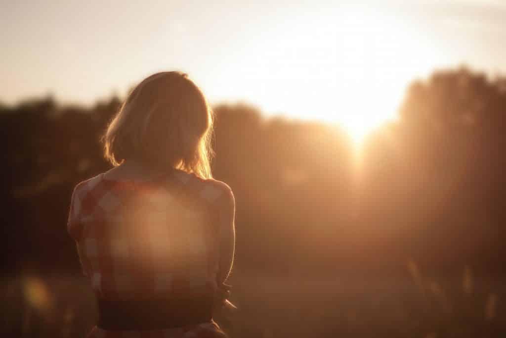 Mulher de cabelos curtos de costas num campo.