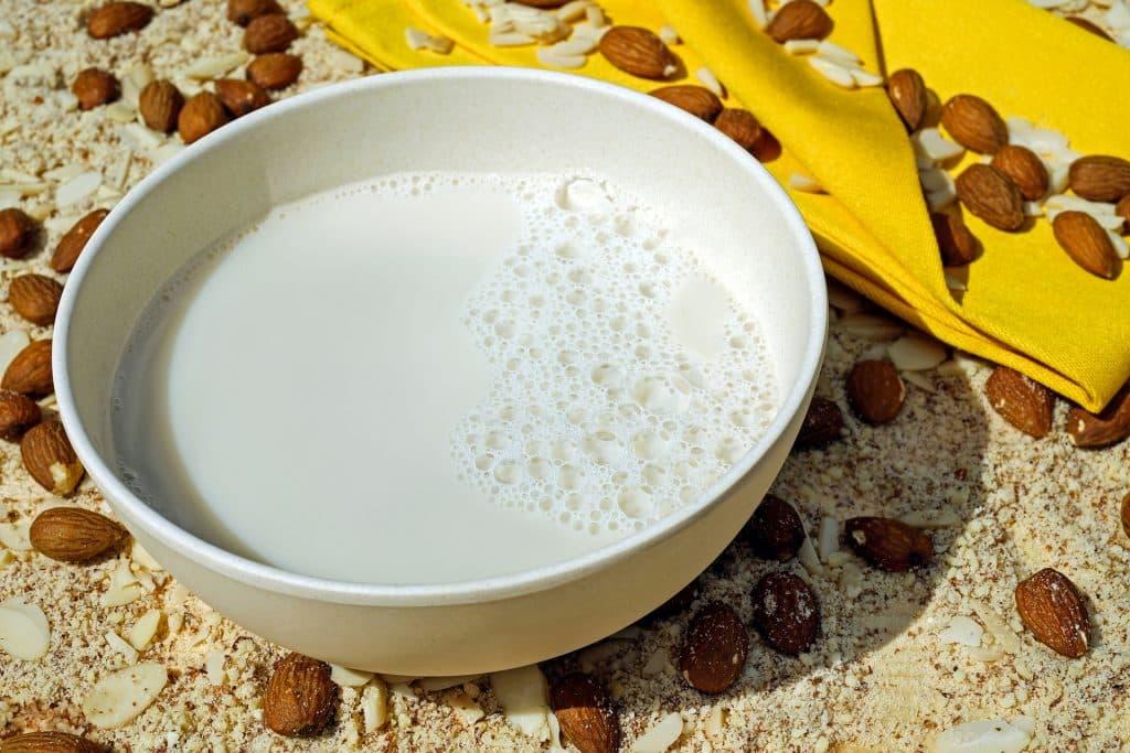 Imagem de uma tigela pequena de porcelana contendo leite de amêndoas. Ao lado várias amêndoas espalhadas sobre a mesa.